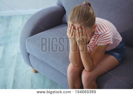 High angle view of girl with hands covering face sitting on sofa at home
