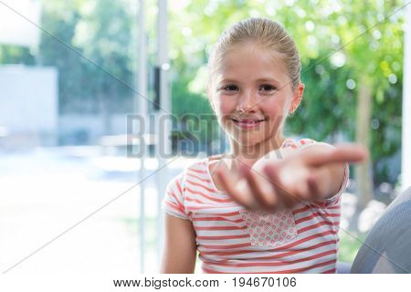 Portrait of girl sitting with arms raised by window at home
