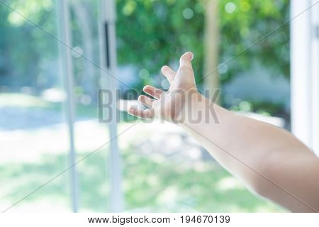 Cropped image of hand reaching window at home