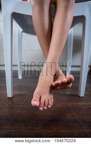 Low section of girl sitting on chair with crossed legs dangling over floor at home