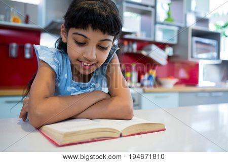 Girl reading novel with arms crossed in kitchen at home