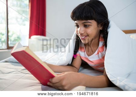Smiling girl reading novel while lying on bed at home