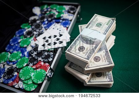 Bundle of US dollars, playing cards and casino chips on poker table in casino