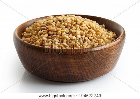 Spelt Groats In Dark Wooden Bowl Isolated On White.