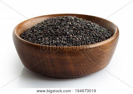 Black Sesame Seeds In Dark Wooden Bowl Isolated On White.