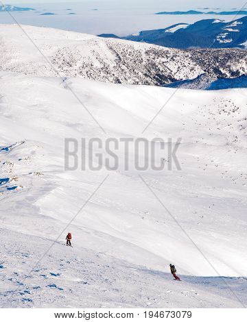 skier and snowboarder ride in snowy mountains