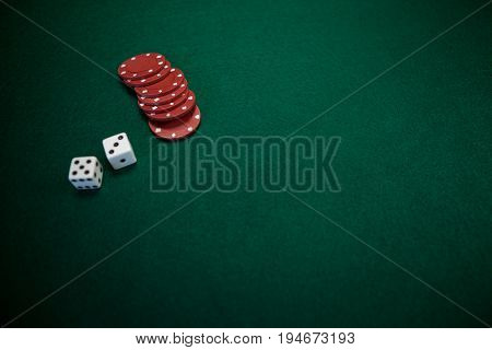 Pair of dice and casino chips on poker table in casino
