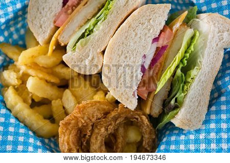 Close up of sliced burger with French fries and onion rings in container