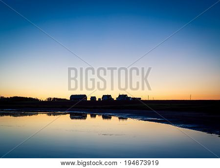 Reflection of a house and barn in Prince Edward Island