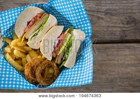 Overhead view of sliced burger with French fries and onion rings in container