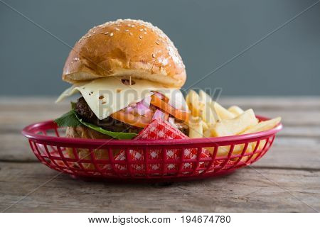 Close up of cheeseburger and French fries in basket on wooden table against wall