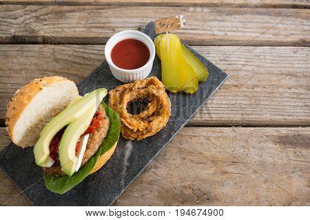 High angle veiw onion rings with burger on slate at table