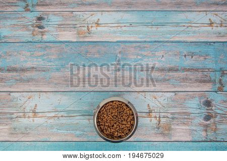 Bowl with cat kibble seen from above on blue scaffolding plank floor