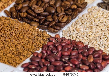 Set of groceries laying horizontal perspective with limited depth of field: roasted coffee beans pearl barley freeze-dried instant coffee dried red seeds of beans.