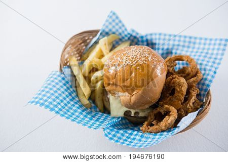 High angle view burger and French fries with onion rings in wicker basket