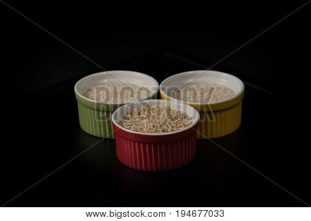 Brown and white rice grains in multicolored ramekins with a black background