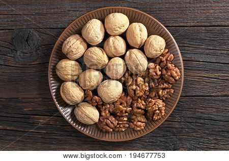 Walnut kernels and whole in plate on dark wooden background top view
