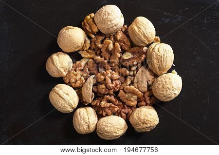 Walnuts and kernels Whole walnuts and kernels on old black metal background top view
