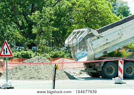 Dump tipper truck unload sand on the street construction site. Rear end of truck.