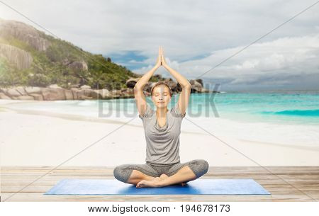 fitness, sport and people concept - woman meditating in yoga lotus pose on mat over exotic tropical beach background