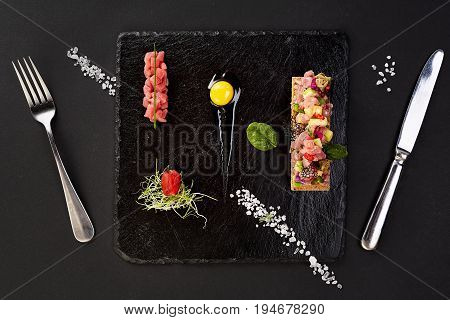 fresh tuna tartar with salt and herbs, studio shot. Fish tartar on black shale. Top view
