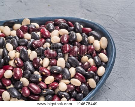 Close up view of raw mixed beans in blue plate on gray concrete background. Mixed of black, red and white beans with copy space.