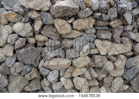 Stone wall background or texture/ Building strengthening/Stones in the iron grid on texture