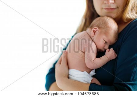 Mother holding her newborn baby daughter after birth on arms. Mum with baby girl, love. New born child cuddling in mama arms. Bonding, family, new life