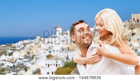 travel, tourism and summer holidays concept - happy couple hugging over oia town on santorini island background