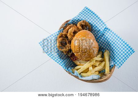 Burger and French fries with onion rings in wicker basket