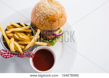 Close up of burger by french fries in container with tomato sauce on plate against white backgroun