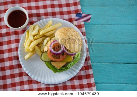 Overhead view of cheeseburger with American flag served with French fries on table