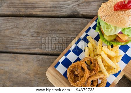 Overhead view of fried onion rings with french fries by burger on cutting board at table