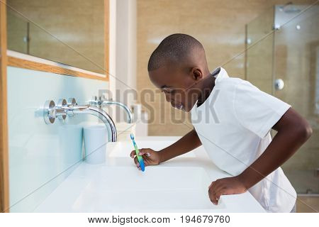 Side view of boy spitting in sink at bathroom