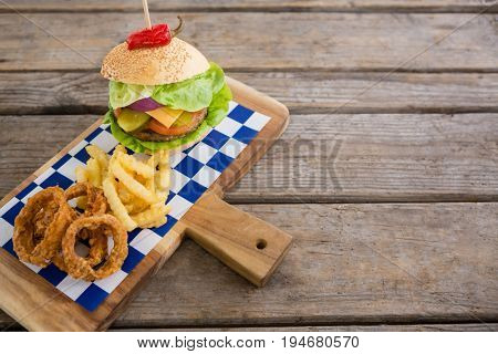 High angle view of onion rings and french fries with burger on cutting board