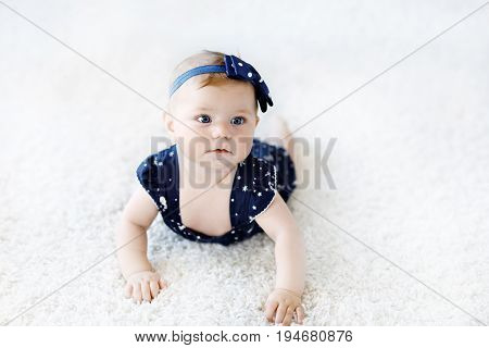 Cute adorable baby girl in blue clothes and headband. New born child, little girl looking at the camera and crawling. Baby learning grab