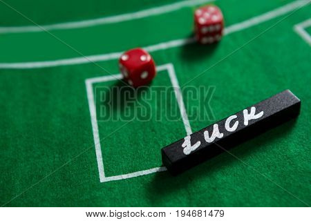 High angle view of text and red dices on blackjack table