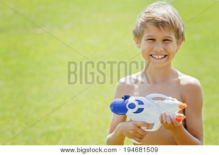 Smiling boy playing with water gun at hot summer day