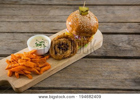 High angle view of hamburger by onion rings with dip and french fries on cutting board
