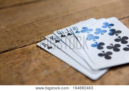 Close-up of clubs cards on wooden table at casino