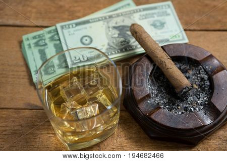 High angle view of whisky and cigar by paper currency on wooden table