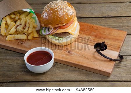 Overhead of hamburger, french fries and tomato sauce on table