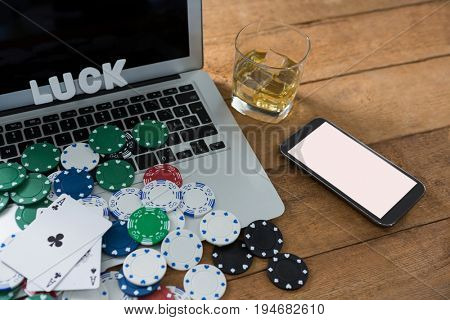 High angle view of scattered chips and aces with technologies on wooden table