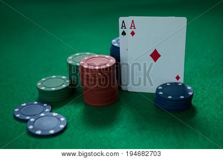 Close-up of aces and chips on green table