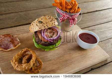 Close-up of hamburger, french fries, onion ring and tomato sauce on chopping board