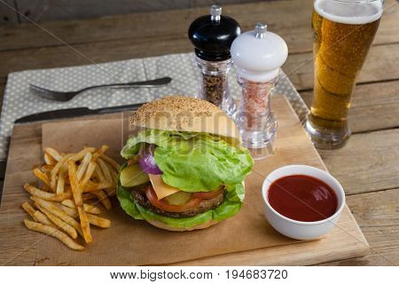 Close-up of hamburger, french fries, tomato sauce and glass of beer on chopping board