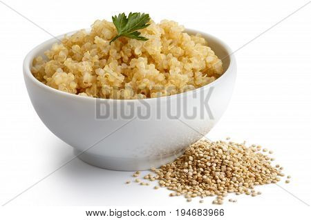 Cooked Quinoa In White Ceramic Bowl Isolated On White With Green Parsley. Spilled Uncooked Quinoa.