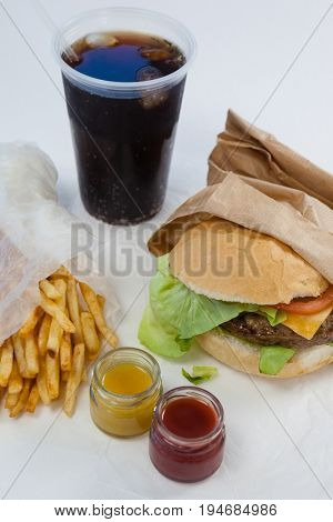 Close-up of hamburger, french fries, sauce and cold drink against white background