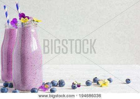 blueberry smoothie or milkshake in bottles with flowers and straw with fresh berries on white wooden background. healthy food for breakfast and snack
