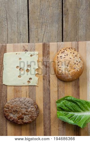 Overhead of ingredient for making hamburger on chopping board